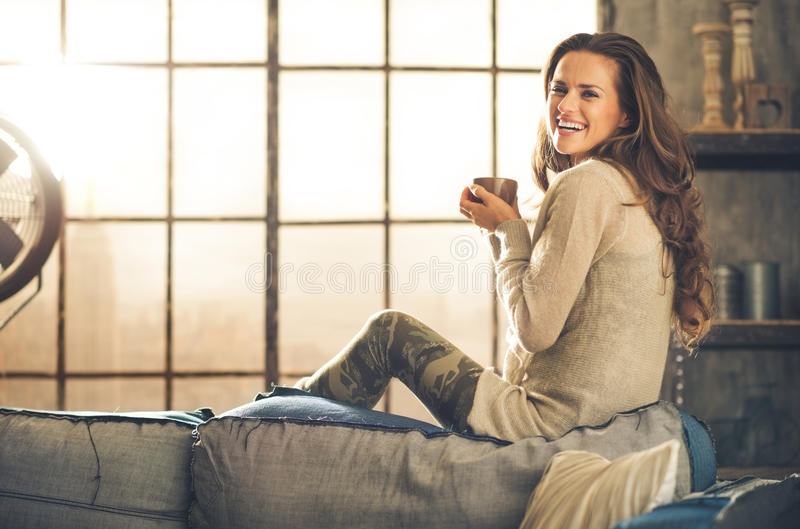 A brunette long-haired woman in a loft living room stock images