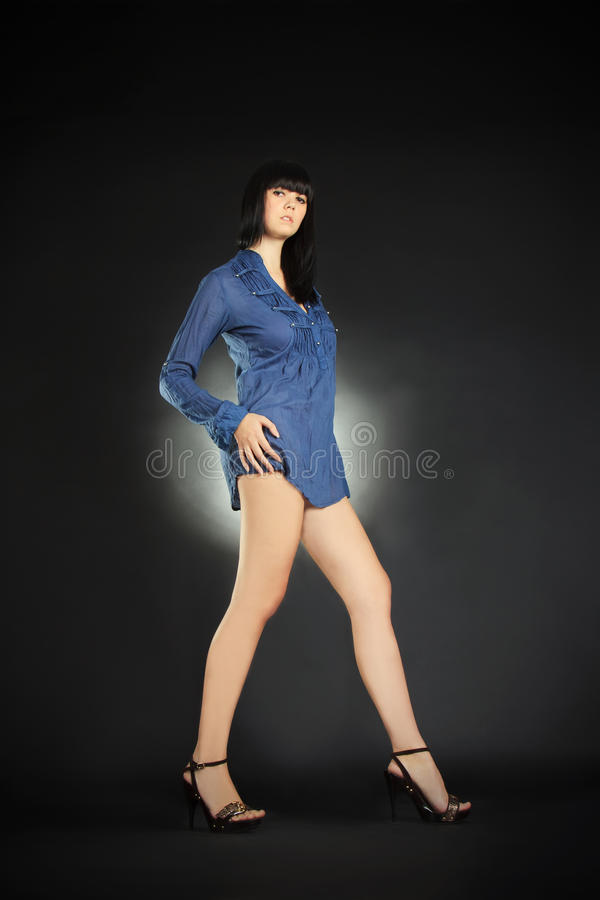 Brunette with long legs posing in the dark royalty free stock photos