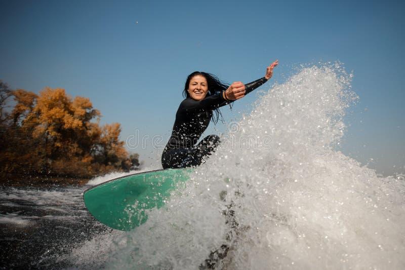 Brunette Mädchen, das auf das grüne wakeboard auf den verbiegenden Knien springt lizenzfreie stockbilder