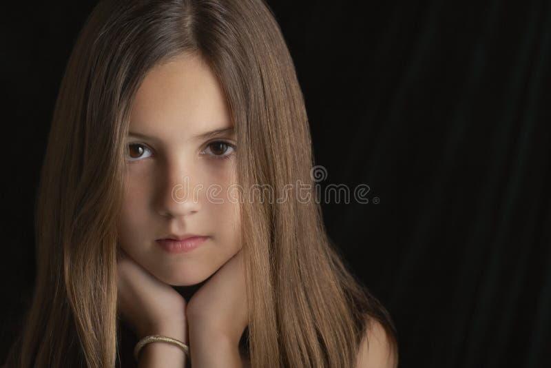 Brunette-Mädchen, das Chin On Hands stillsteht lizenzfreie stockfotos