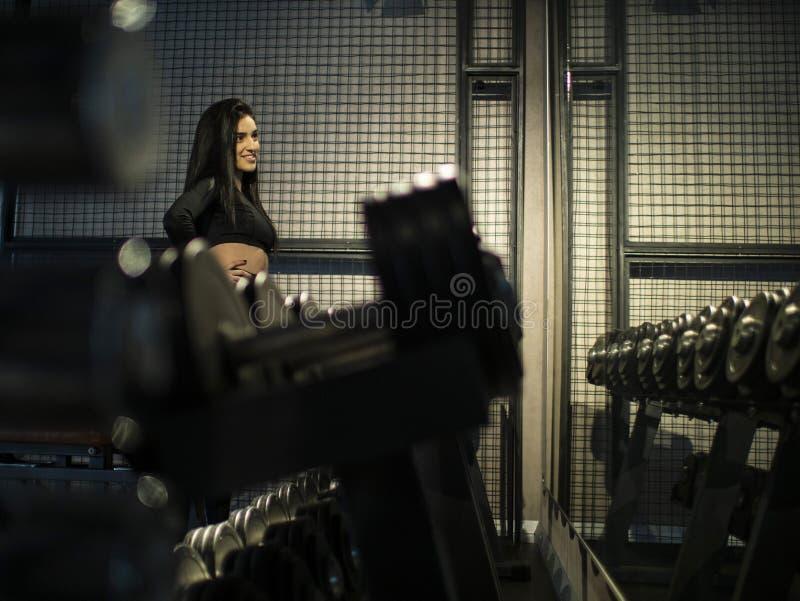 Brunette Mädchen der Eignung in der schwarzen Sportkleidung, die das Regal mit Dummköpfen in der Turnhalle an gegen den Spiegel b stockfotografie