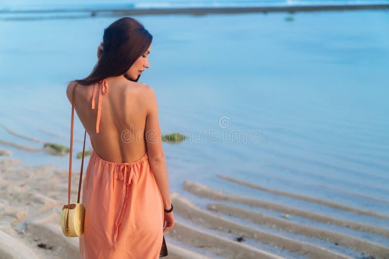 Brunette Mädchen der Rückseitenansicht mit dem langen Haar im Strandkleid und Weidentasche auf dem langen Bügel, der am Strand au stockbilder