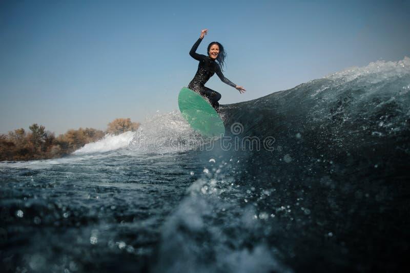 Brunette Mädchenreiten auf dem grünen wakeboard auf den verbiegenden Knien stockfotos