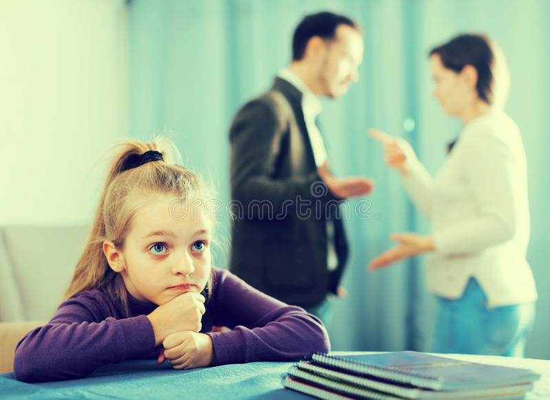 Brunette male and female arguing with each other. While their daughter at home stock image