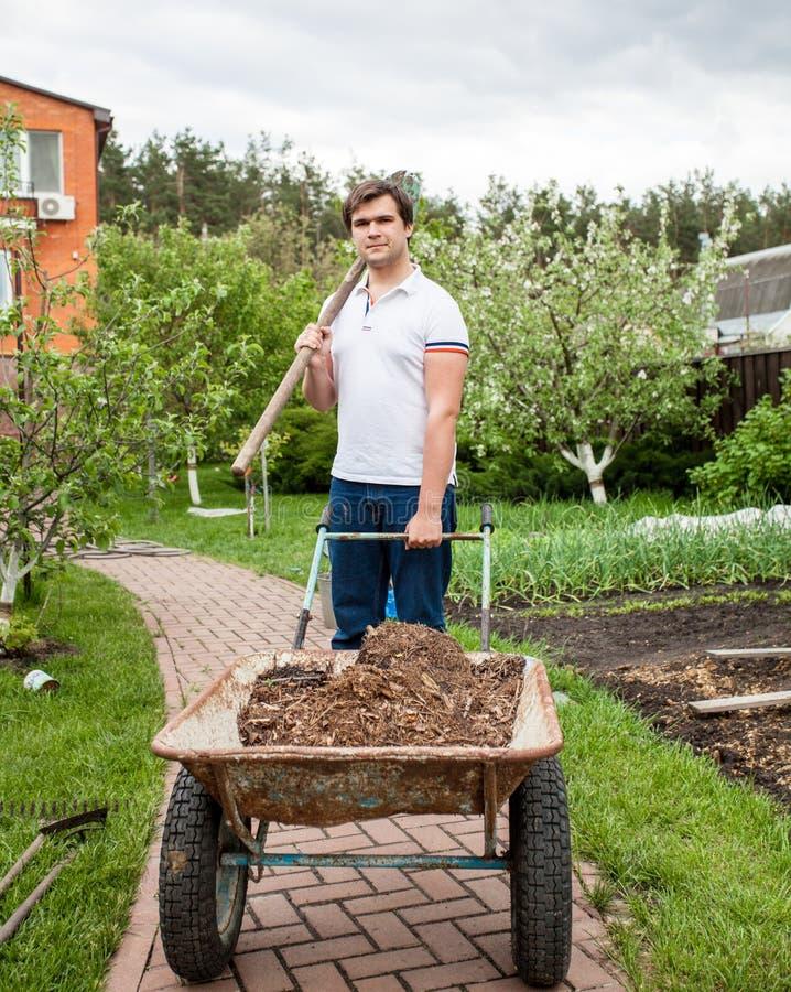 Brunette man holding shovel and wheelbarrow stock image