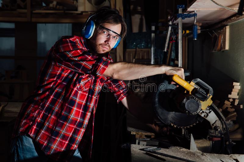 Brunette man profession carpenter builder saws with a circular saw a wooden board. royalty free stock image