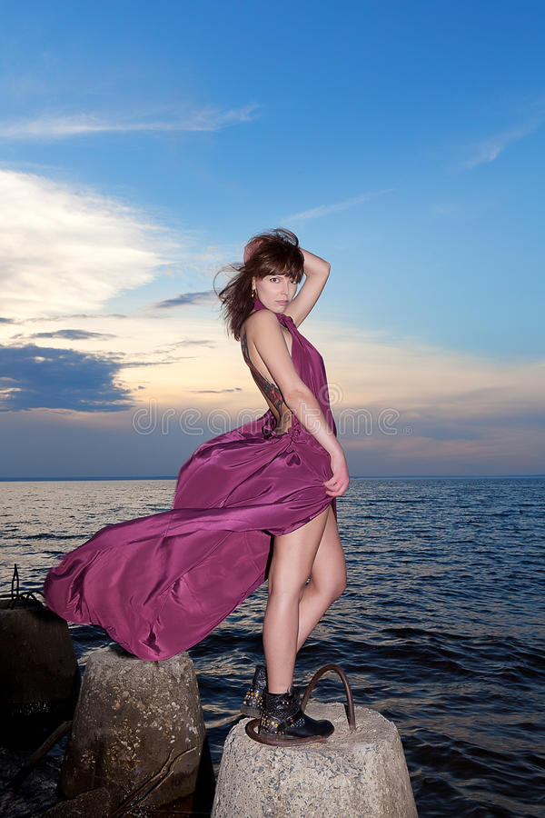 Brunette in maroon dress on bank of river. Against evening sky stock photography