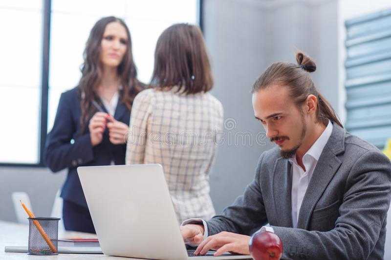 A man is working on a laptop and two girls of his colleague are standing nearby. royalty free stock photo