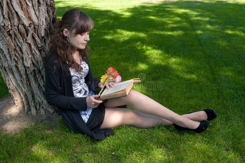 Brunette met bloemen die boek op gras lezen stock afbeelding