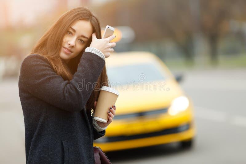 Brunette met koffie dichtbij taxi stock afbeelding