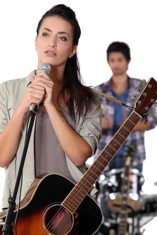 Brunette with microphone. Brunette with a microphone rehearsing royalty free stock photo