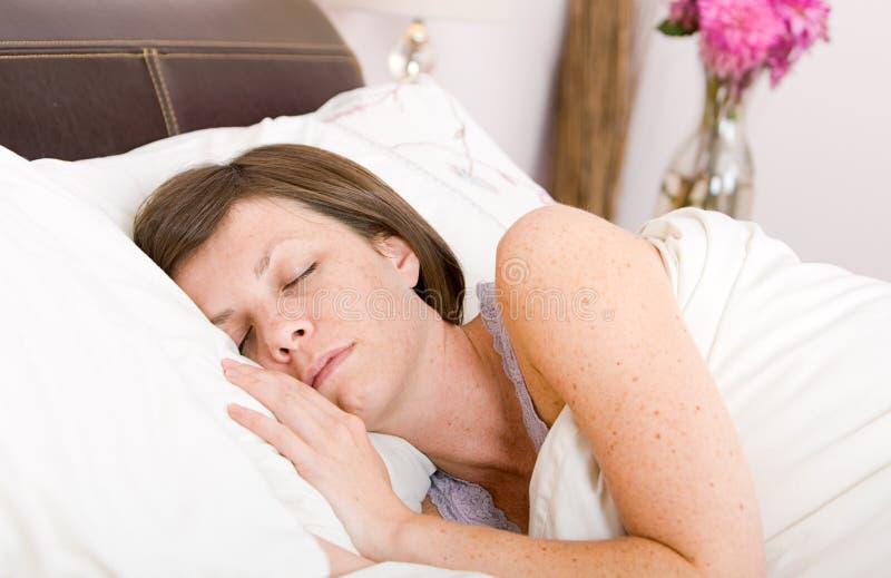 Brunette mignon en sommeil dans son bâti image stock