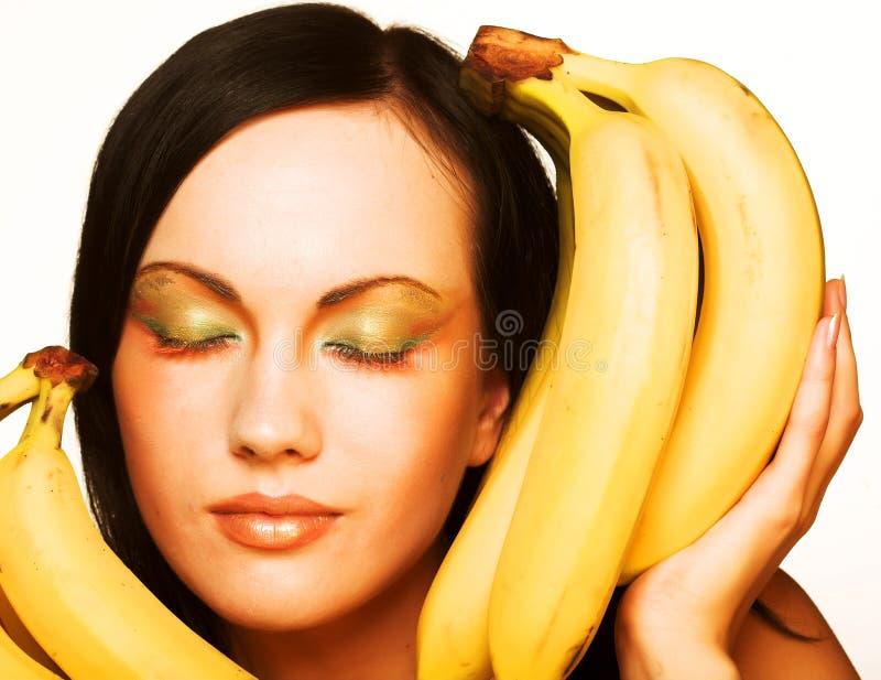 Brunette mit Bananen auf einem weißen Hintergrund stockfotos