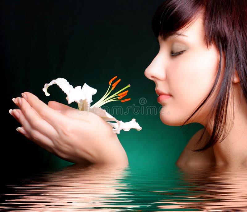Brunette mit Blumen der weißen Lilie im Wasser lizenzfreie stockfotografie