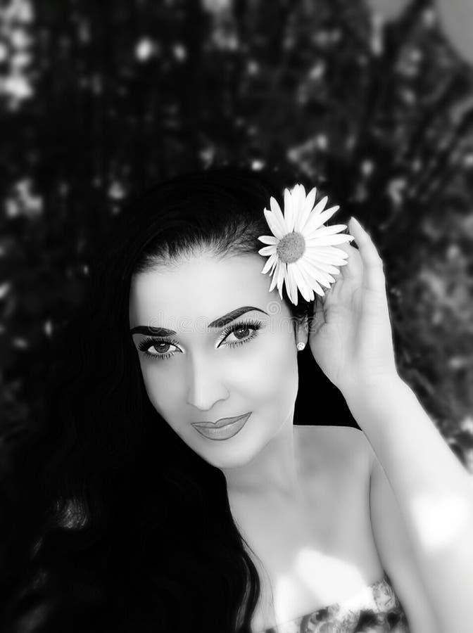 Brunette mit Blumen in ihrem Haar lizenzfreie stockfotografie