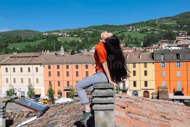 Brunette mit dem langen Haar, das auf einem Kamin sitzt lizenzfreie stockbilder