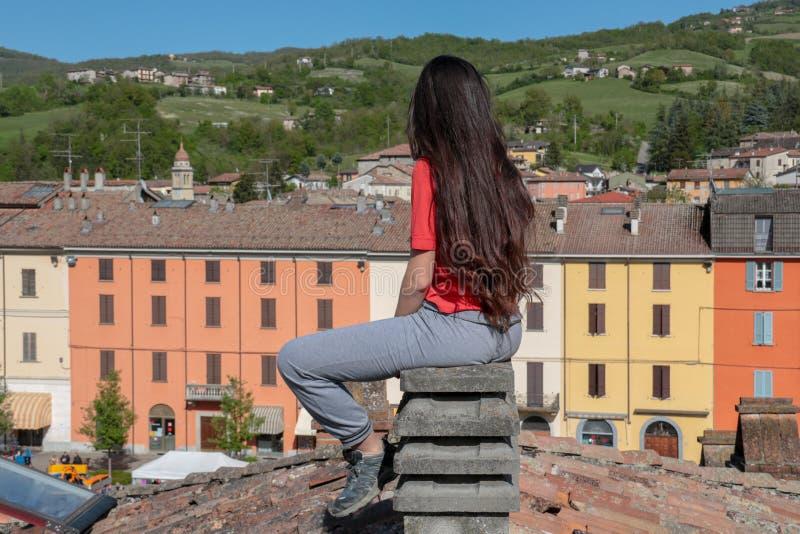 Brunette mit dem langen Haar, das zurück auf einem Kamin sitzt lizenzfreies stockbild