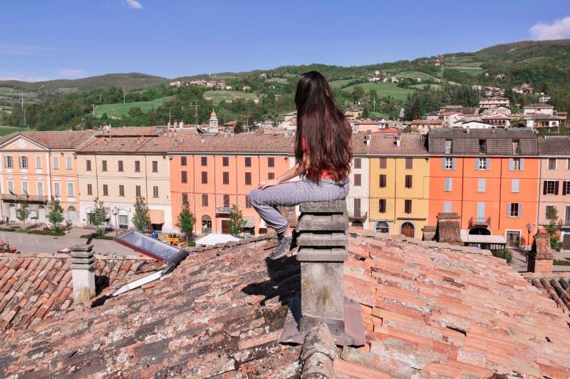 Brunette mit dem langen Haar, das zurück auf einem konkreten Kamin sitzt lizenzfreies stockbild