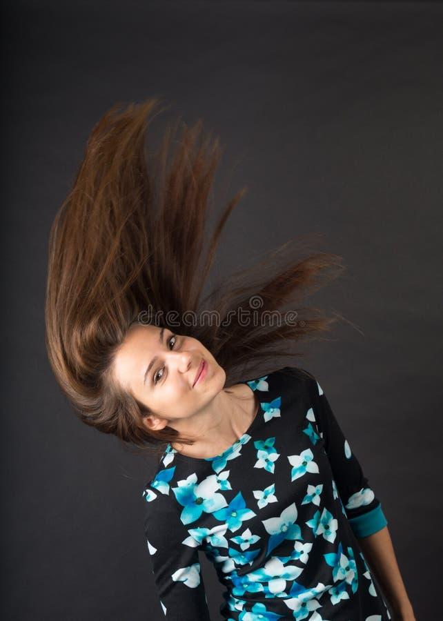 Brunette mit sich entwickelnden Haar Foto im Studio auf einem dunklen Hintergrund stockfoto