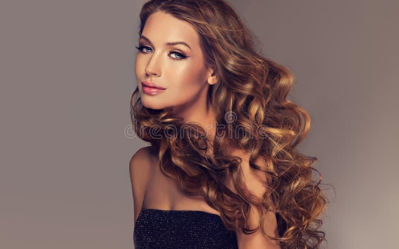 Brunette mit umfangreicher, glänzender und gelockter Frisur lizenzfreie stockfotografie
