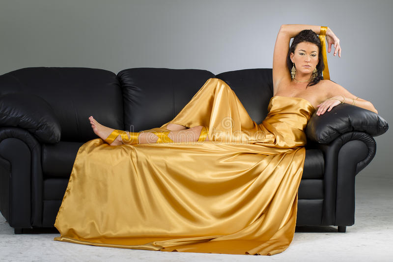 Brunette Model In A Gold Dress On A Sofa royalty free stock photo