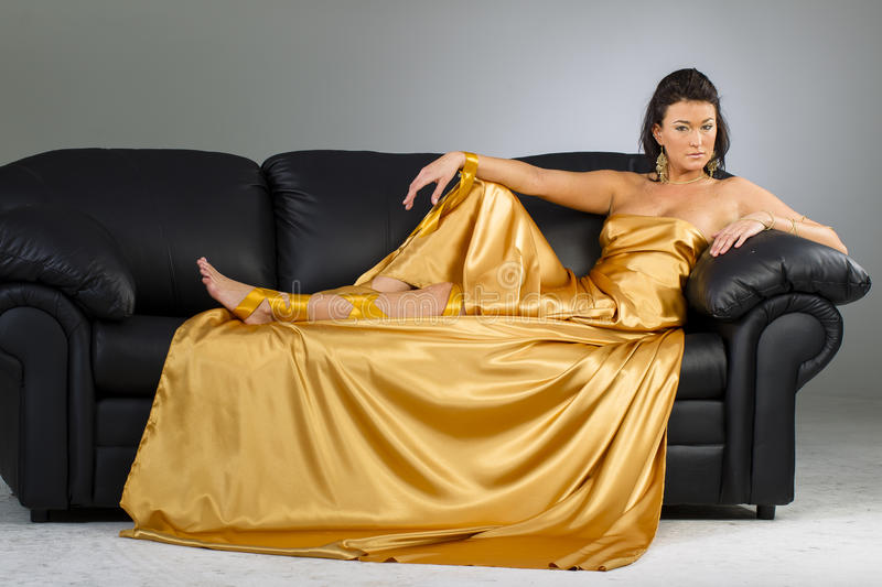 Brunette Model In A Gold Dress On A Sofa royalty free stock photos