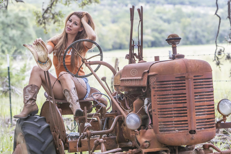 Brunette Model With a Tractor. Brunette model with an old tractor stock photo
