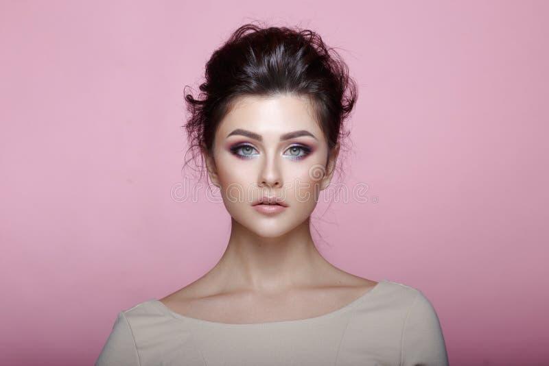 Brunette Modell der Schönheitsmode mit dem reizend Make-up, welches die Kamera lokalisiert auf rosa Hintergrund in den warmen Tön stockbild