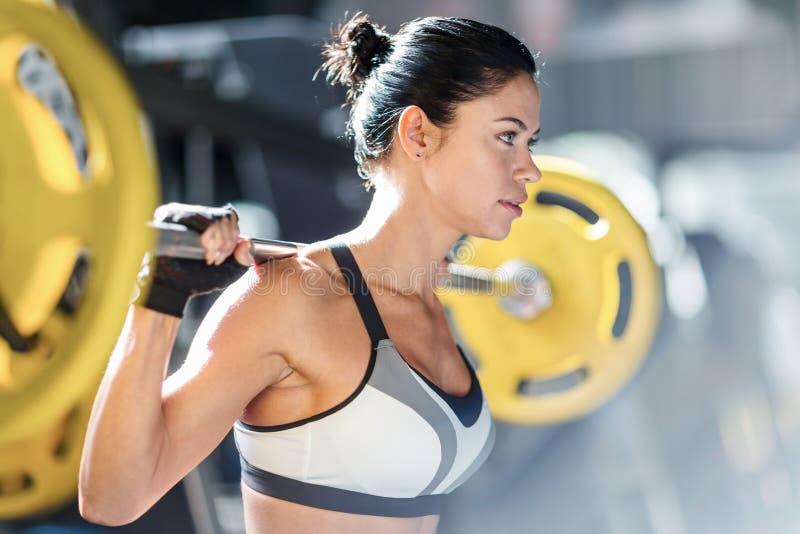 Brunette Muscular Woman Weightlifting Bar stock photos