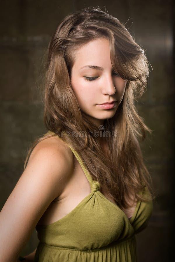 Brunette novo bonito que levanta no vestido verde. imagens de stock