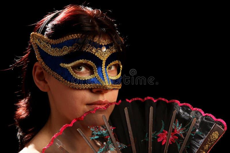 Brunette novo com máscara venetian e ventilador espanhol foto de stock
