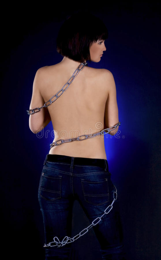 Brunette with nude back in chains. Over black background stock photography