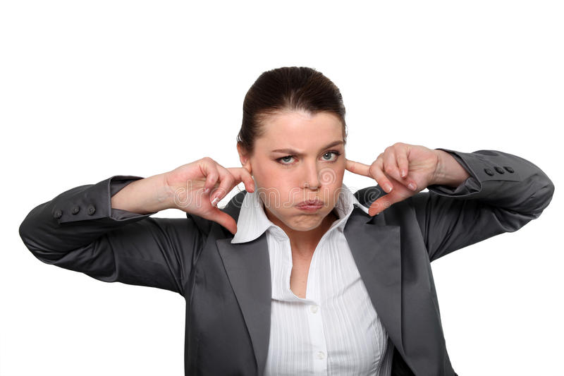 Brunette office worker. With fingers in ears stock photography