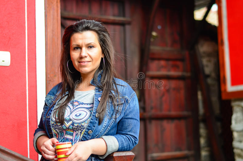 Brunette. Outdoor portrait of a pretty young woman drinkig coffee against red wall stock image