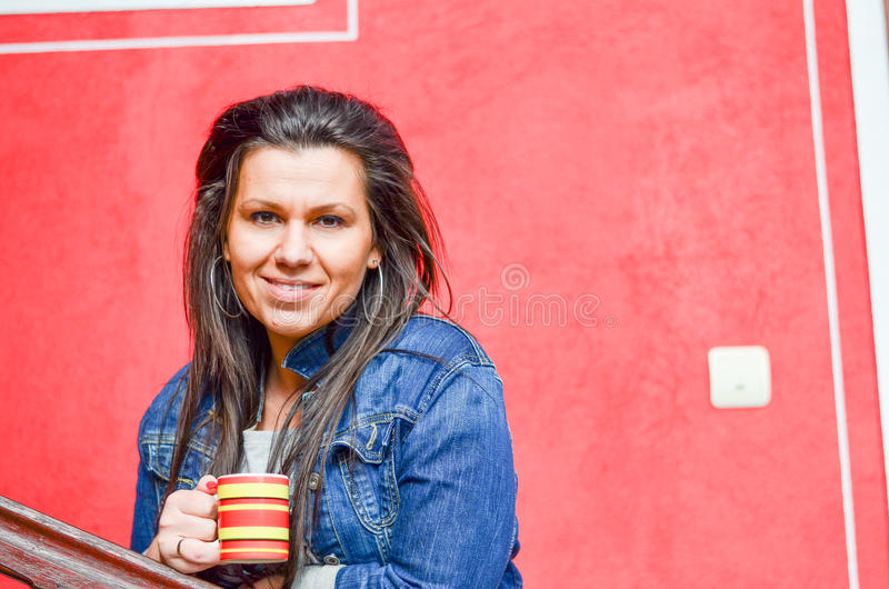 Brunette. Outdoor portrait of a pretty young woman drinkig coffee against red wall royalty free stock image