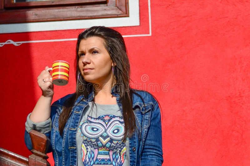 Brunette. Outdoor portrait of a pretty young woman drinkig coffee against red wall stock images