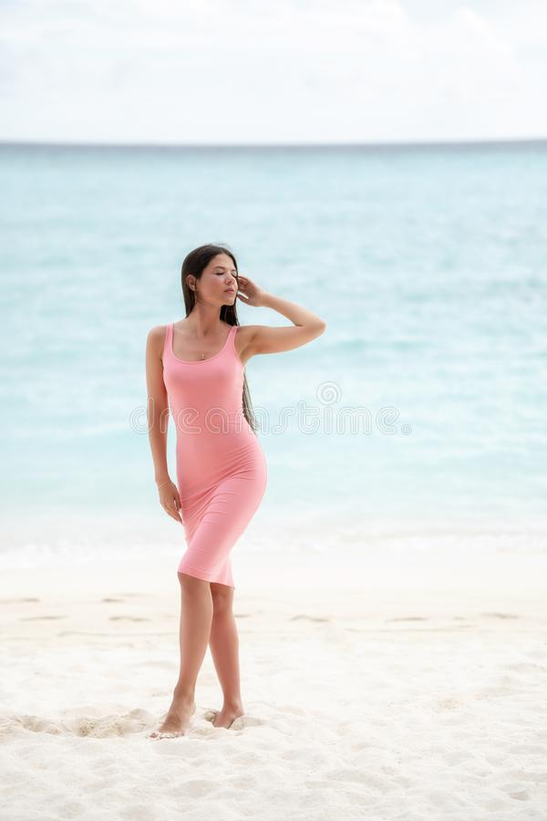 The brunette in a pink fitting dress walks on a snow-white beach royalty free stock image