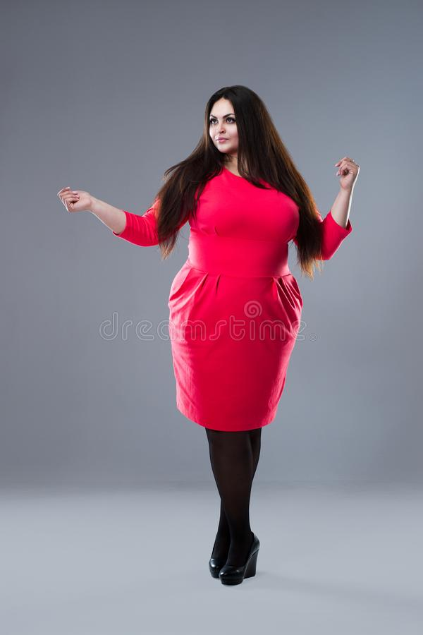 Brunette plus size fashion model in red dress, fat woman with long hair on gray background, body positive concept stock images