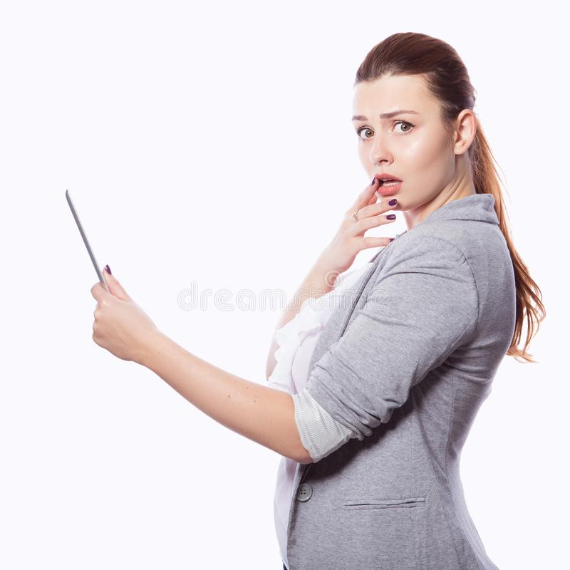 Brunette plus size woman in smart casual outfit jacker and blou. Se on an isolated white background. She holds gadgets in ger hands: tablet and phone. Freelance royalty free stock image