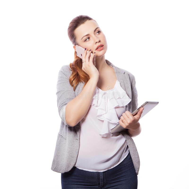 Brunette plus size woman in smart casual outfit jacker and blou. Se on an isolated white background. She holds gadgets in ger hands: tablet and phone. Freelance stock photo