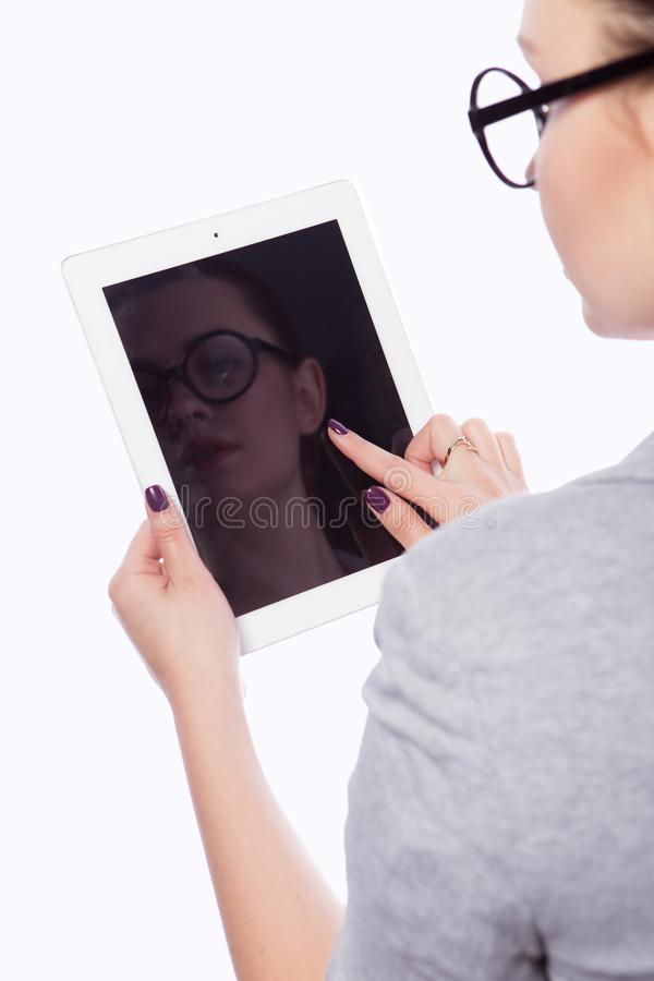 Brunette plus size woman in smart casual outfit jacker and blou. Se on an isolated white background. She holds gadgets in ger hands: tablet and phone. Freelance royalty free stock photos
