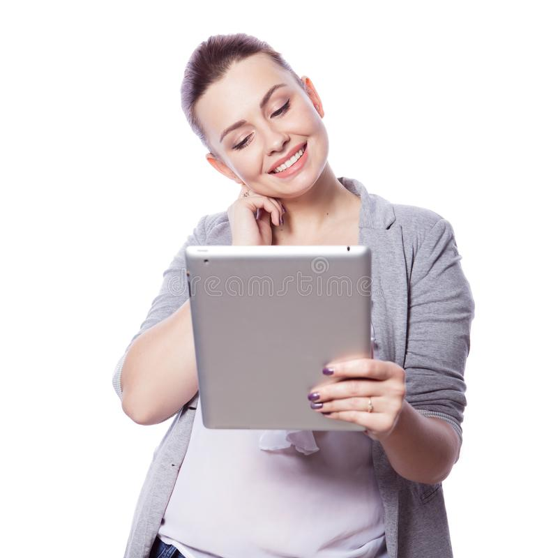 Brunette plus size woman in smart casual outfit jacker and blou. Se on an isolated white background. She holds gadgets in ger hands: tablet and phone. Freelance stock image