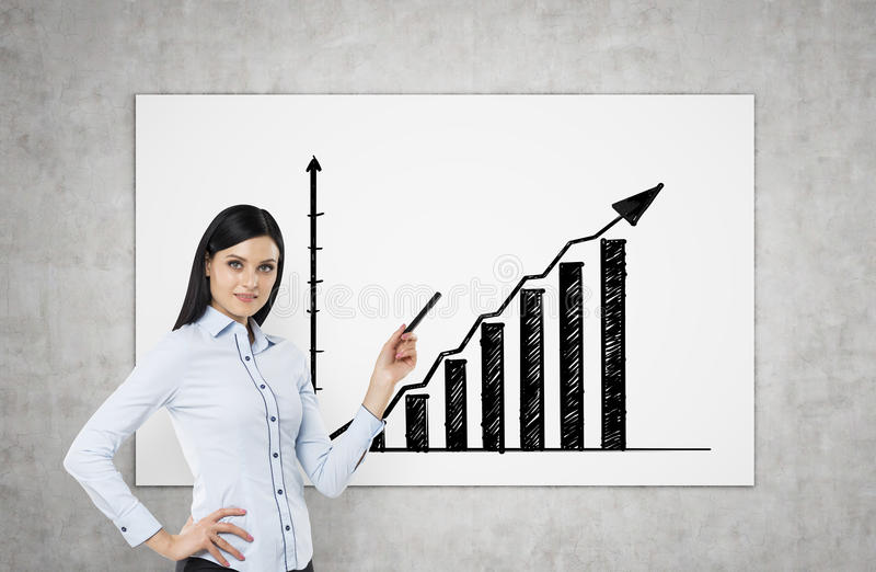 A brunette is pointing out bar chart. A concept of successful business presentation. stock images