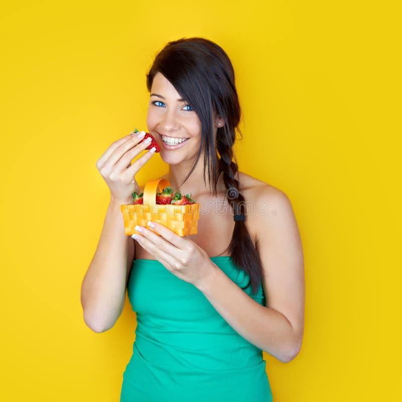 Brunette que come morangos fotografia de stock