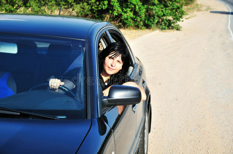 Brunette que conduz um carro fotografia de stock