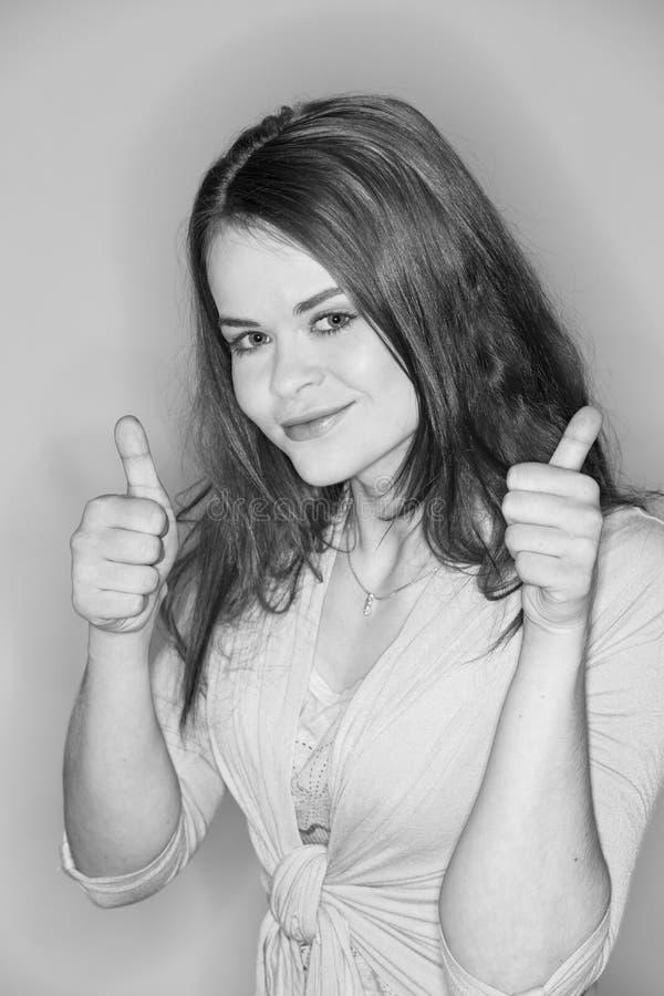 Brunette que mostra os polegares acima fotos de stock royalty free
