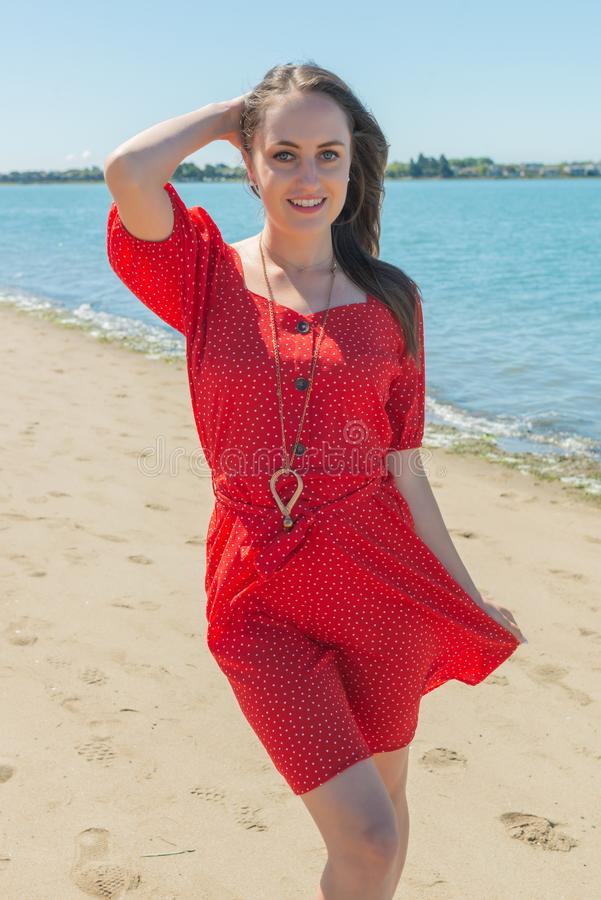 Brunette in red on a beach royalty free stock image