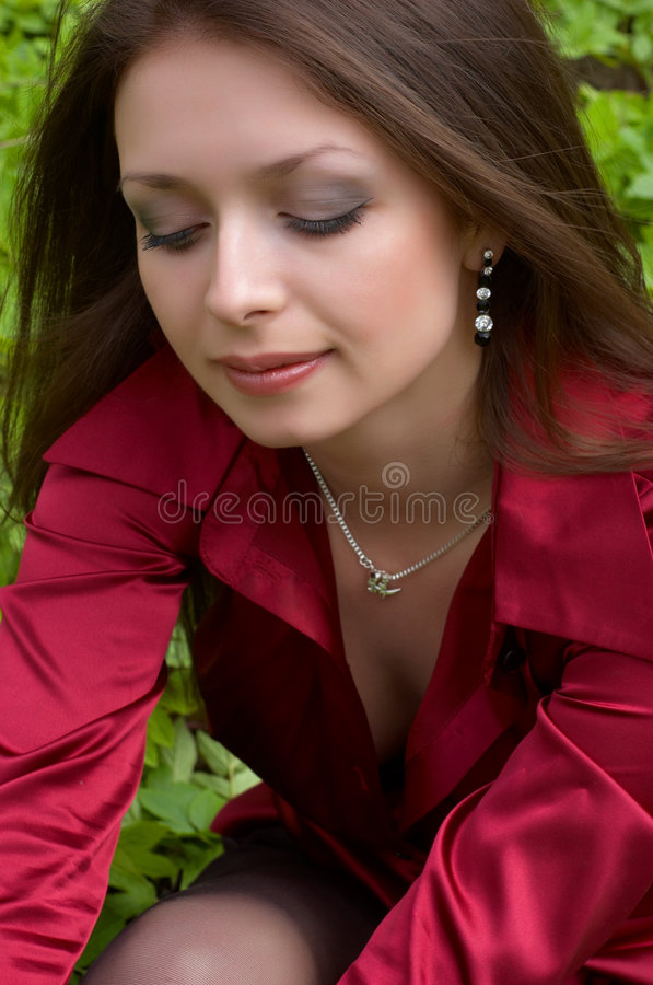 Brunette in red sitting on the stock photo