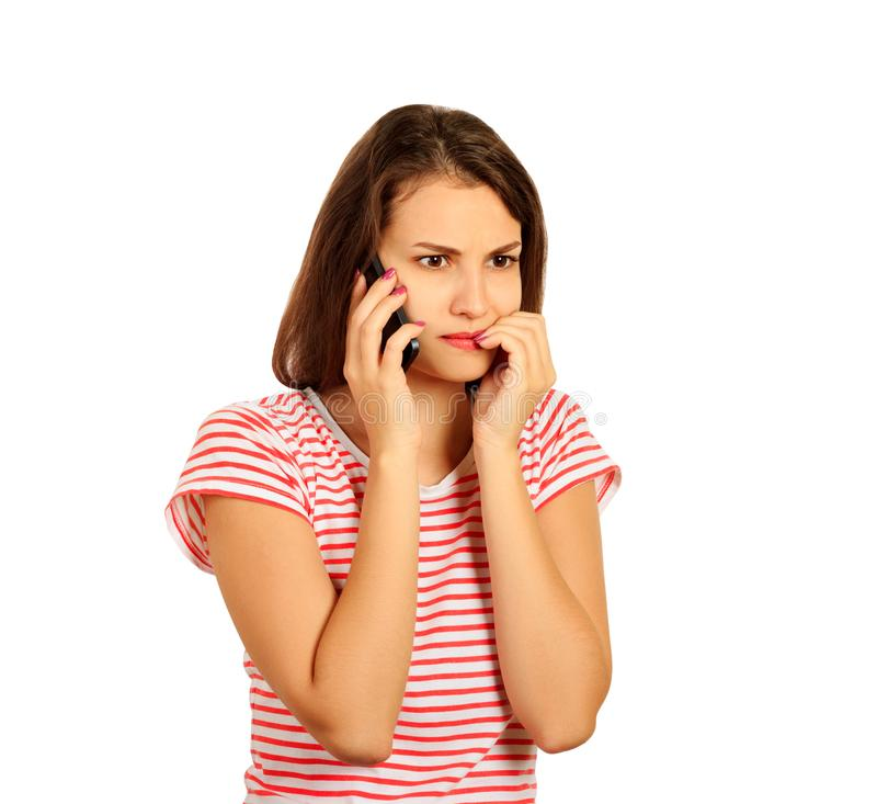 The brunette in a red striped T-shirt speaks on the smartphone and looks worried about the bad news. emotional girl isolated on wh royalty free stock photography