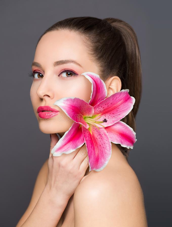 Brunette Schönheit mit bunter Blume lizenzfreie stockbilder